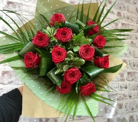 12 High Quality Naomi Red Roses Hand tied  and presented in an eco recycled glass vase.
