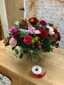 Deluxe red and pink hand tied bouquet in an included fishbowl vase.